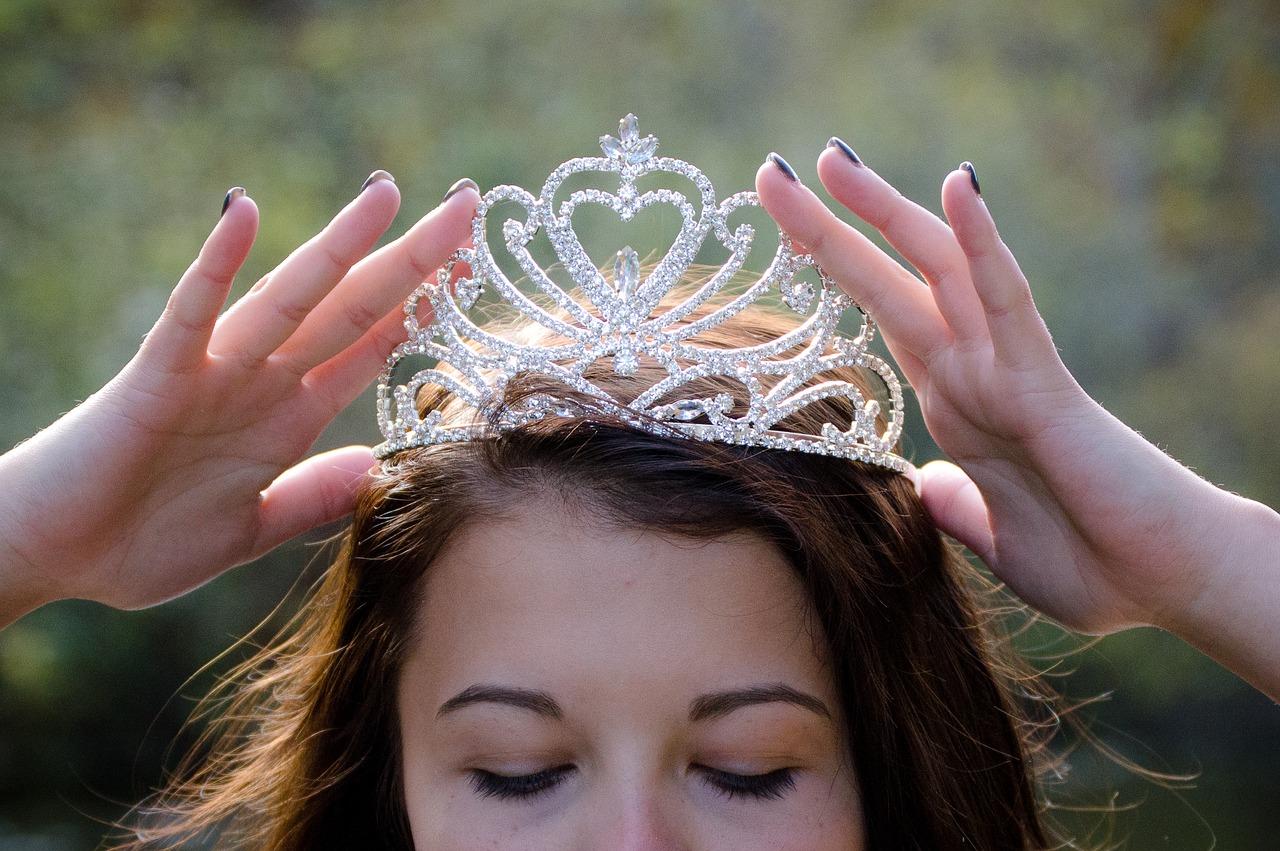 Woman putting on a tiara.
