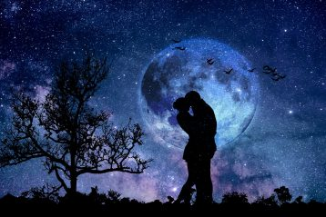 Silhouetted couple embracing at night in front of the moon.