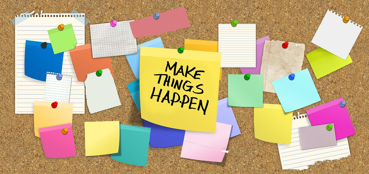 """Bulletin board with sticky notes, including one that reads, """"Make Things Happen""""."""