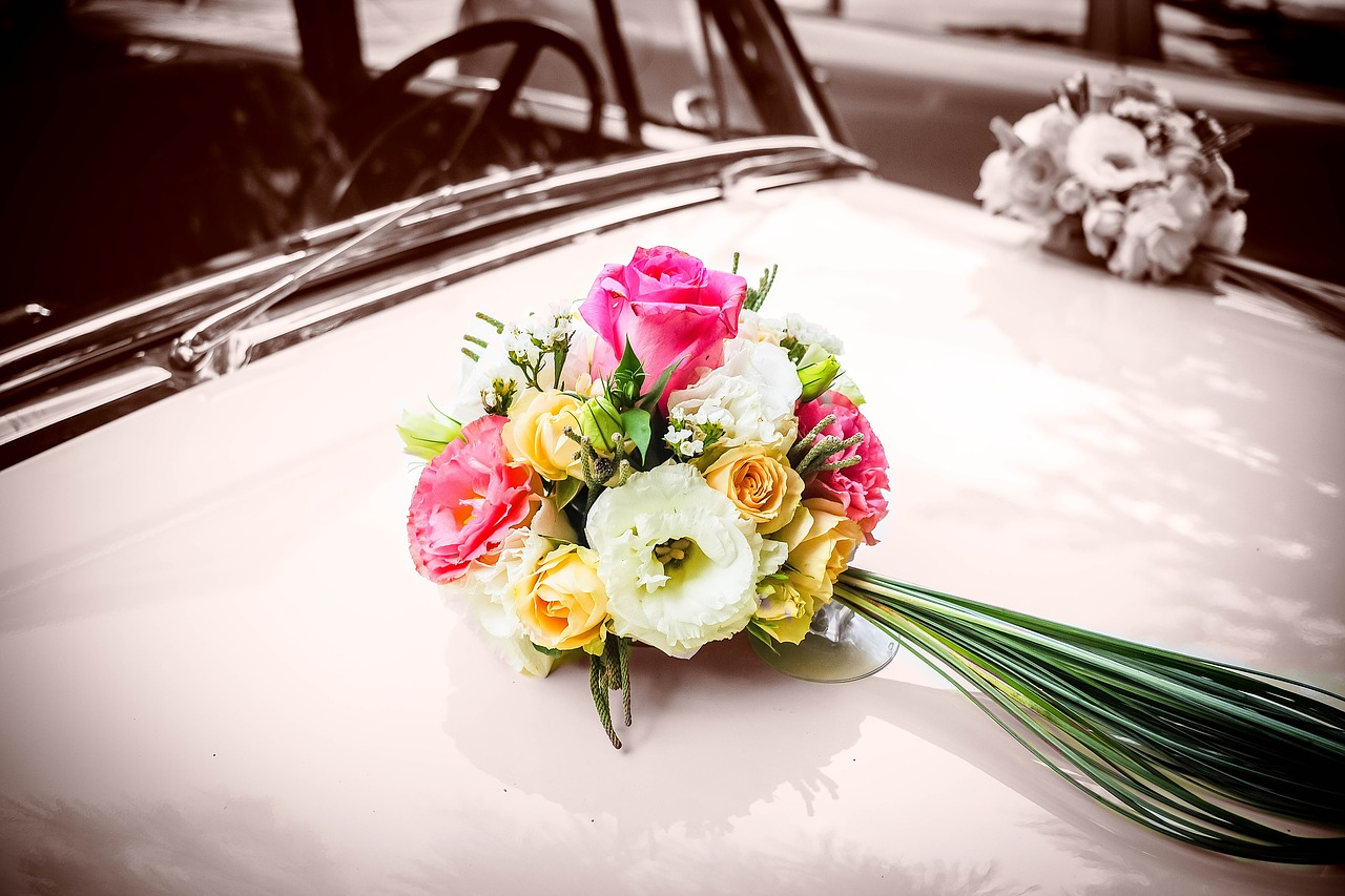 Wedding bouquet atop an old car.