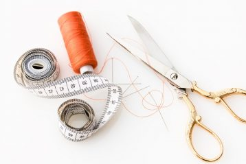 Measuring tape with scissors and spool of thread.