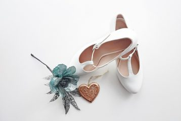 A pair of bridal shoes and a flower.