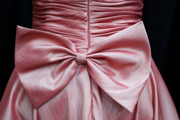 The back of a bridesmaid's dress which has a big bow on it.
