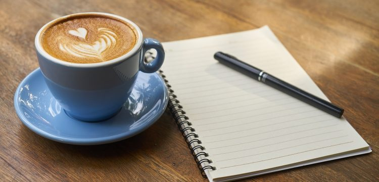 A cup of coffee sitting next to a notebook and pen.