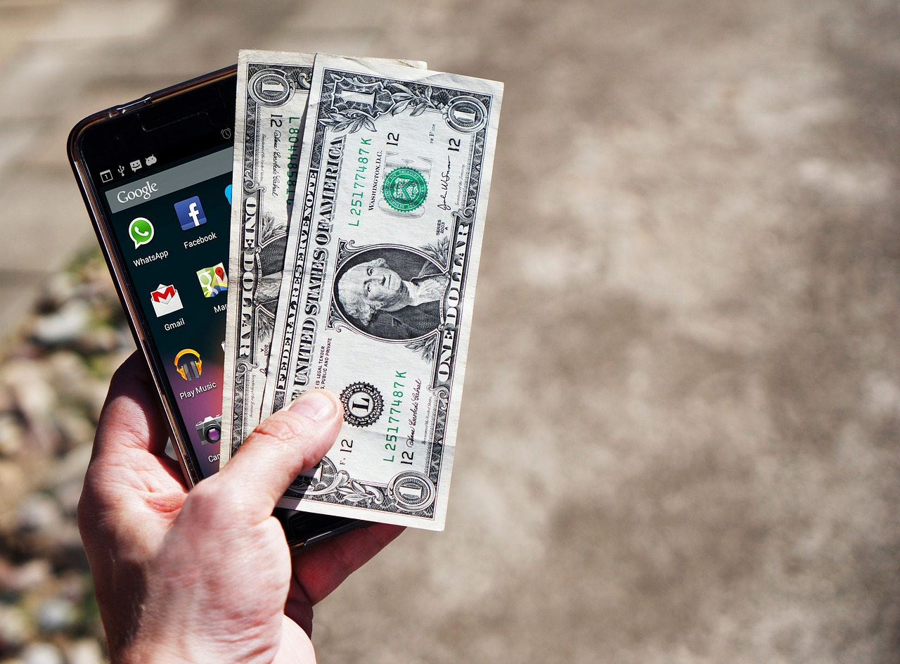 A hand holding a cell phone and two one dollar bills.