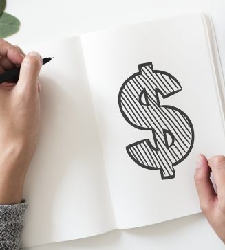 A hand drawn picture of a dollar sign on a notebook.