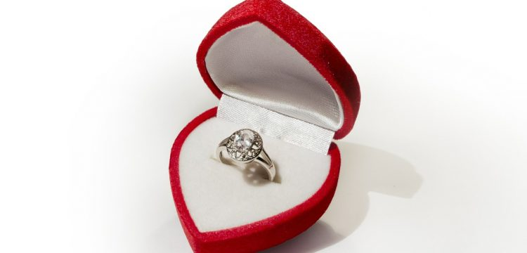 An engagement ring in a heart shaped jewelry box.