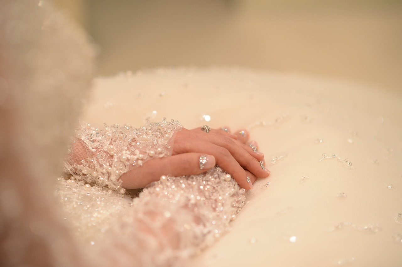 A bride's hands resting on her lap.