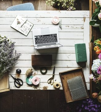 A work table strewn with flowers and a laptop in a flower shop.