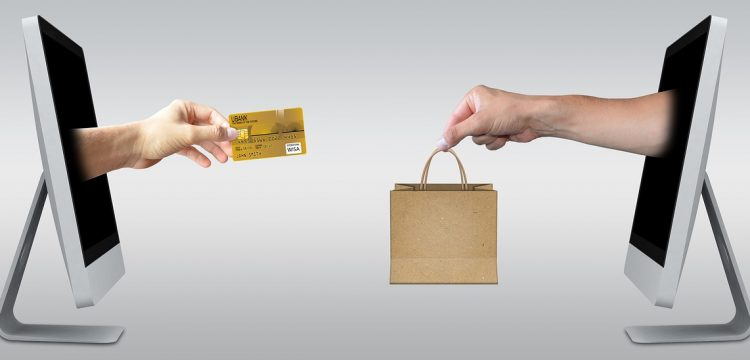 A hand with a credit card reaching out to a hand with a shopping bag.