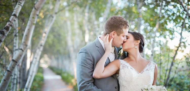 Bridal couple kissing outside by a row of trees.