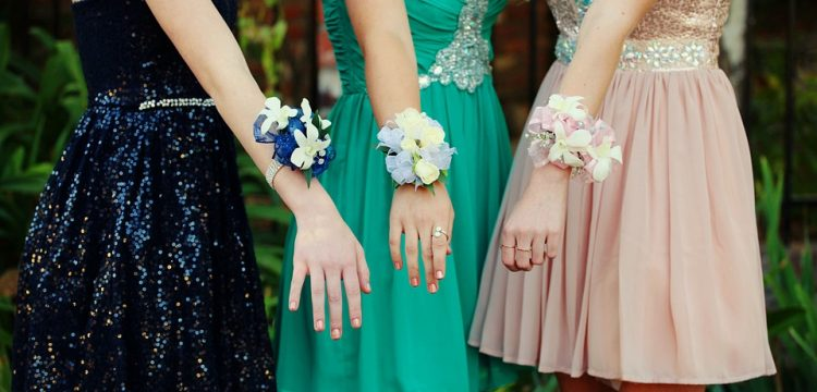 Three girls wearing prom dresses holding out their arms with corsages on them.