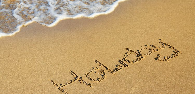 """The word """"holiday"""" written in the sand."""