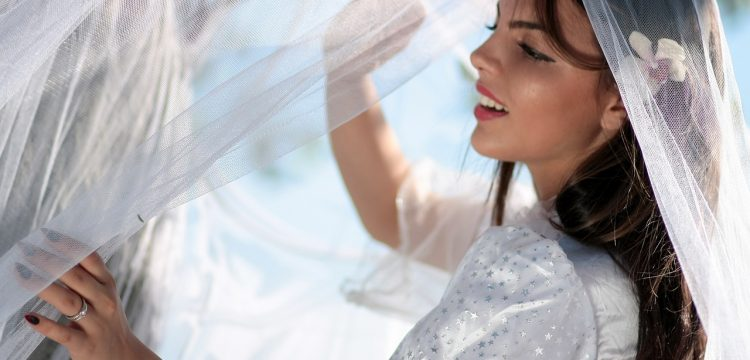 Bride holding a wedding veil.