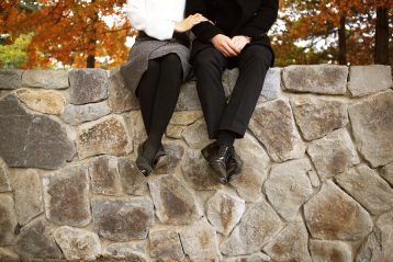 A couple sitting on a stone wall, linking arms.