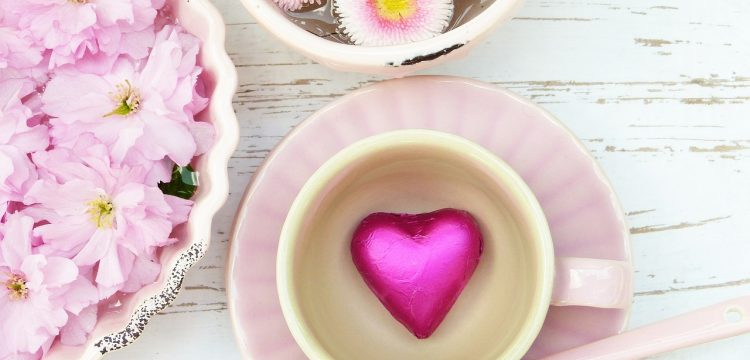 Pink flowers in bowls and a cup on a pink saucer with a pink heart in the center.