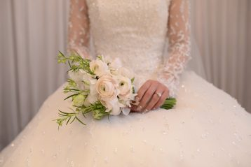 Bride holding flower bouquet.