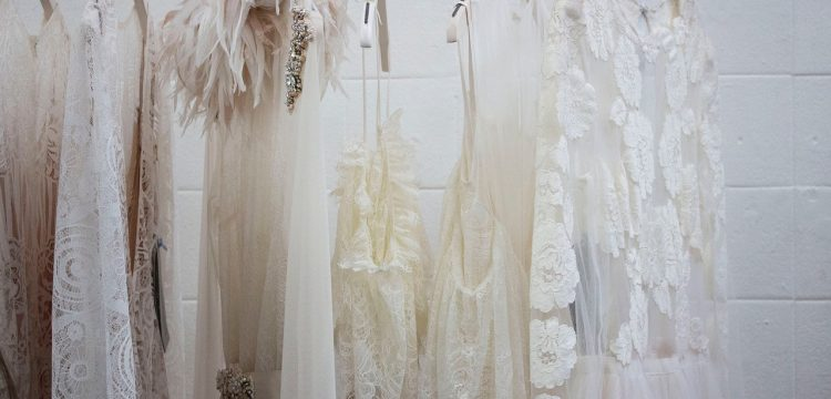 A row of wedding gowns hanging.