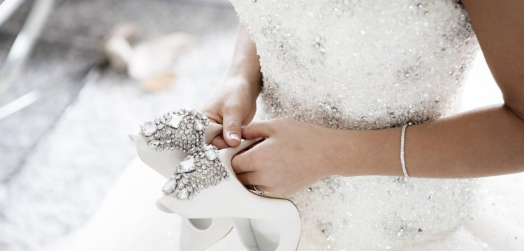 A bride in a beautiful gown, holding wedding shoes.