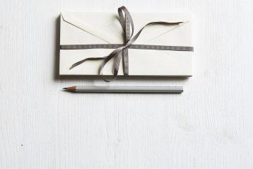A wedding invitation and pen.