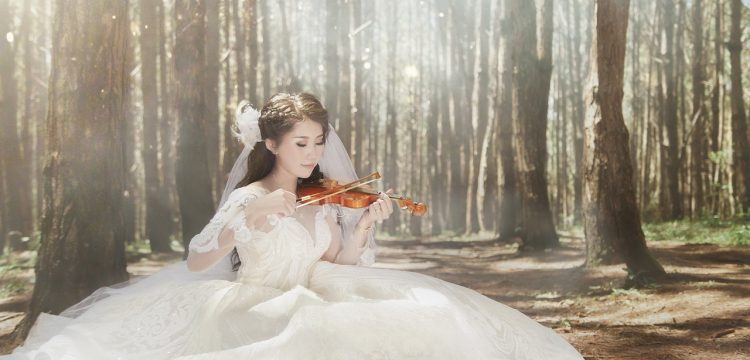 A bride playing a violin in the woods.