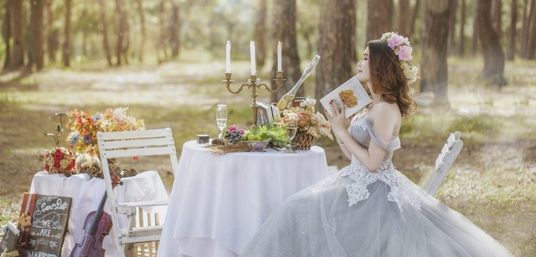 Smiling bride holding a book sitting in the forest at a food and drink laden table.
