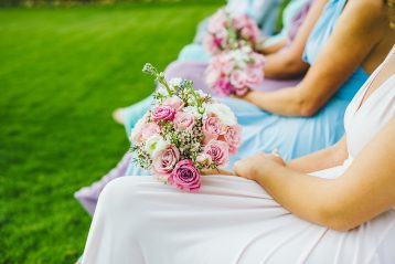 A row of bridesmaids sitting with a bride and with flower bouquets.