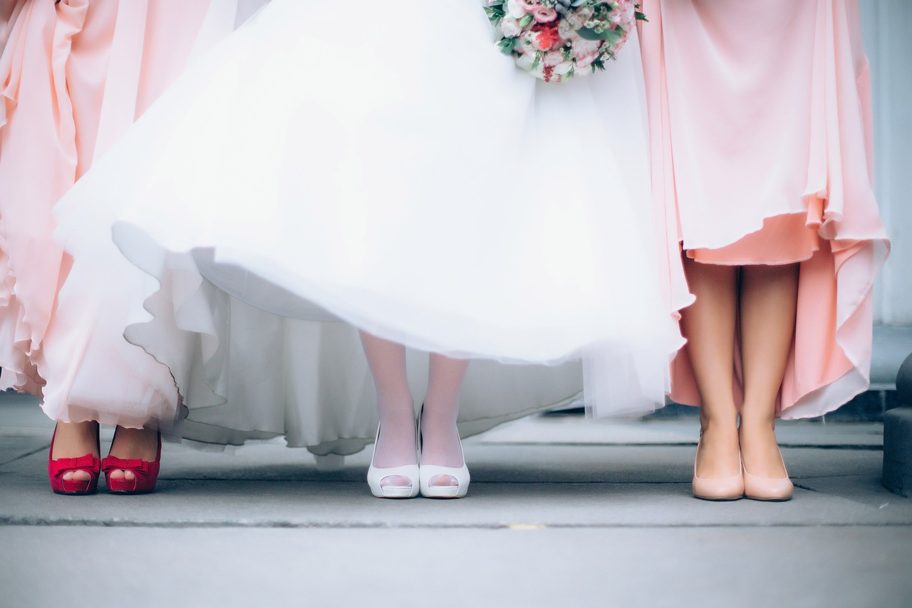 A bride standing with her bridesmaids, shown from the waist down.