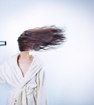 Woman blow drying her hair.