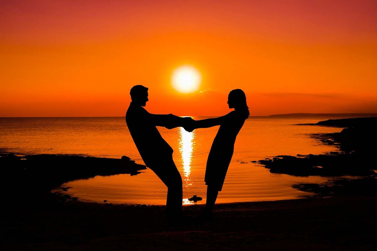 A couple standing on the beach holding hands while the sun rises.