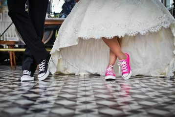 Bride and groom wearing sneakers with their wedding attire.