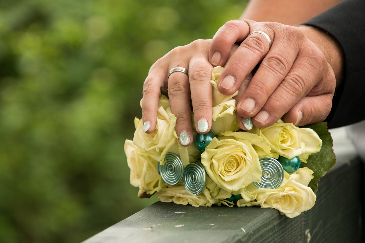 A bride and groom's hands resting on a bridal bouquet.