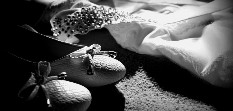 Black and white photo of a wedding dress and shoes.