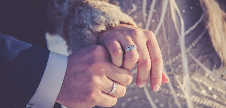 Man and woman wearing wedding rings and holding hands.