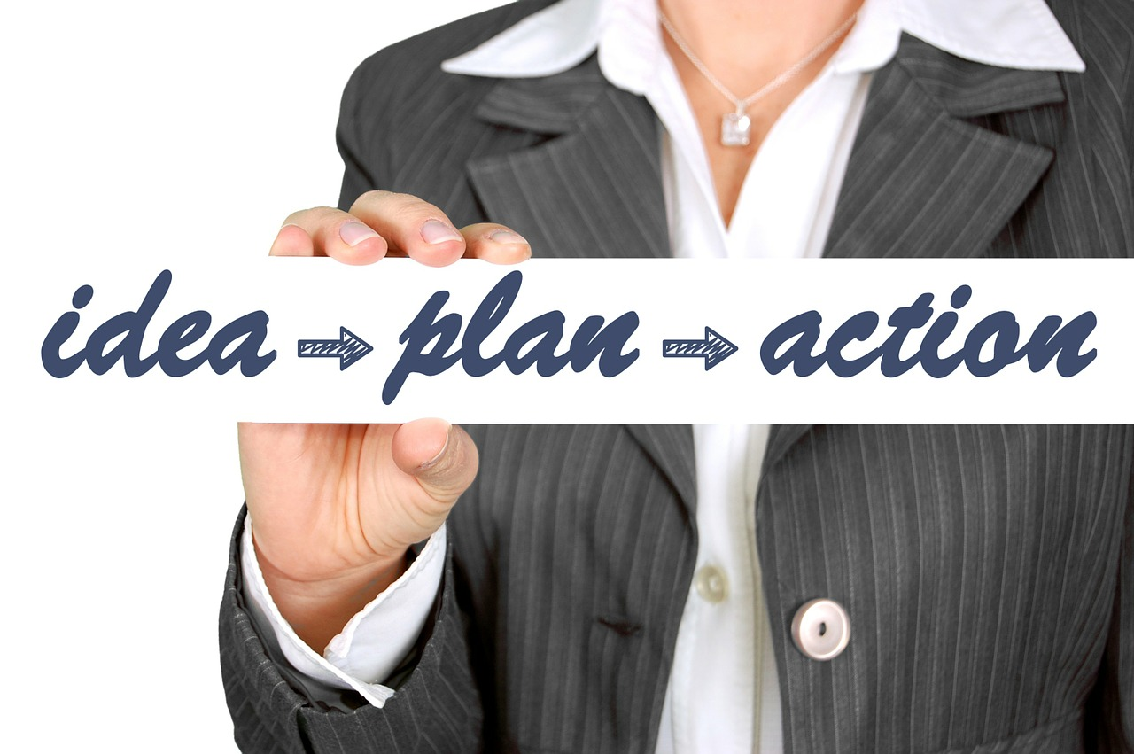 """A businesswoman holding a sign reading """"idea, plan, action""""."""