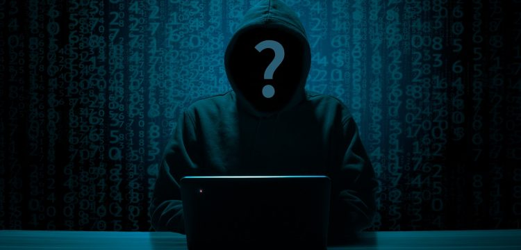 Dark picture of a hooded person sitting in front of a computer.