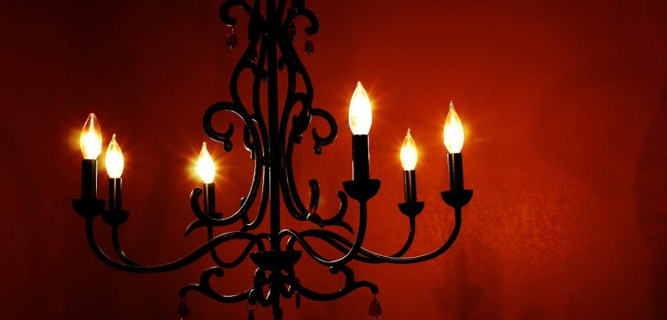 Goth inspired chandelier in front of a deep red wall.