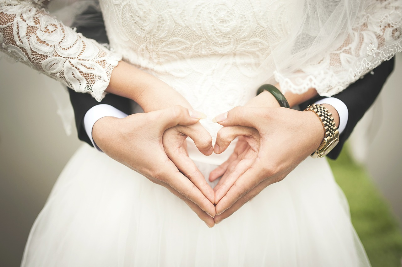 A bride and groom with intertwined hands forming a heart.