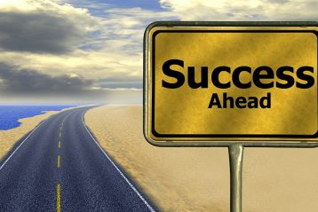 "A road with a sign that reads, ""Success Ahead""."