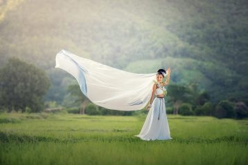 Bride in field with her veil flying in the wind.
