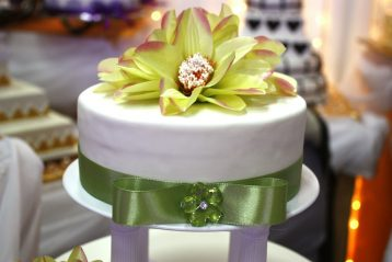 A green and white wedding cake with a large flower on top.