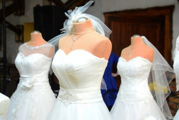 Three wedding dresses on mannequins.