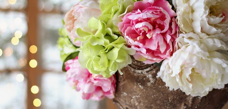 Green, pink, and white wedding flowers in a vase.