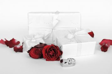 Wedding gifts sitting next to red roses.