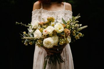 Boho-type bride holding a bouquet in front of her.