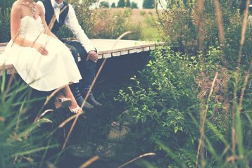 Bride and groom sitting on a small bridge, feet dangling.