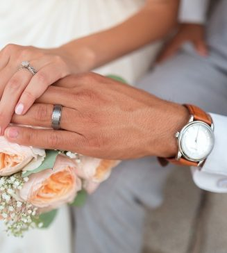 Bride and groom's hands with wedding rings on them.