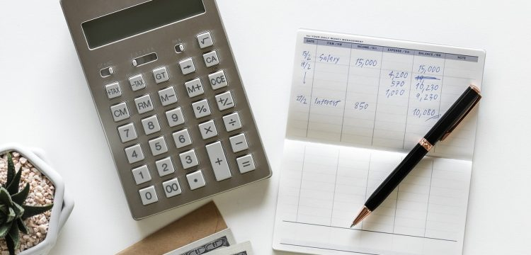Checkbook with calculator and money.
