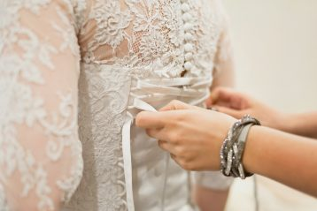 Someone tying the corset on a lacy wedding gown.