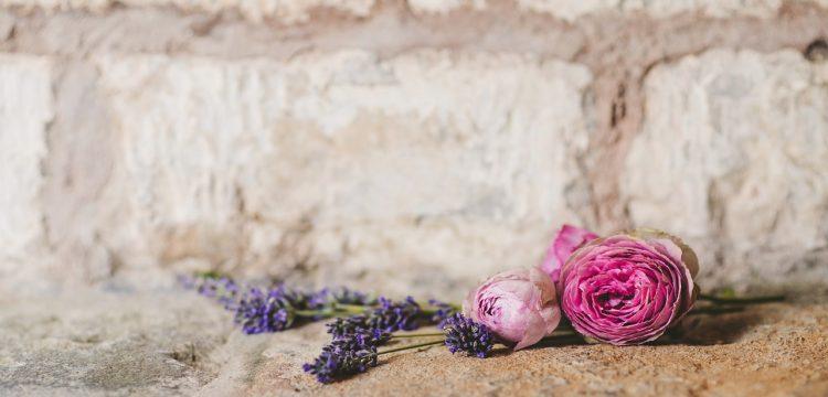 Flowers lying on a brick wall.